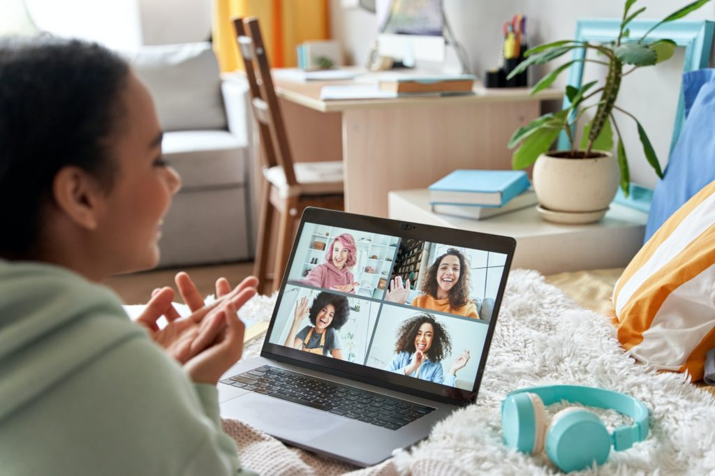 African teen girl talking with friends on distance video group call in bedroom.