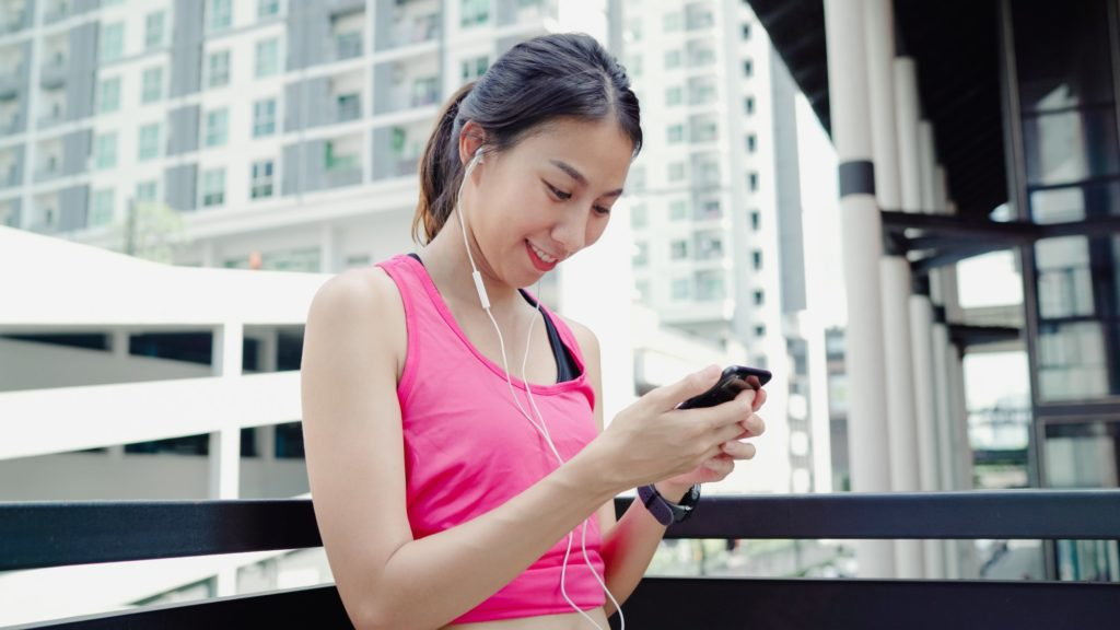 Asian Athlete woman using smartphone for listen to music while running.