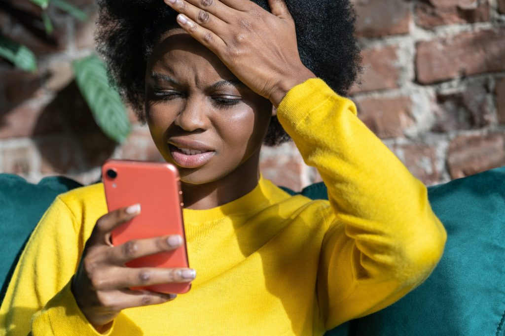 Confused Afro-American woman doing facepalm gesture touching head with palm gets bad news. Epic fail