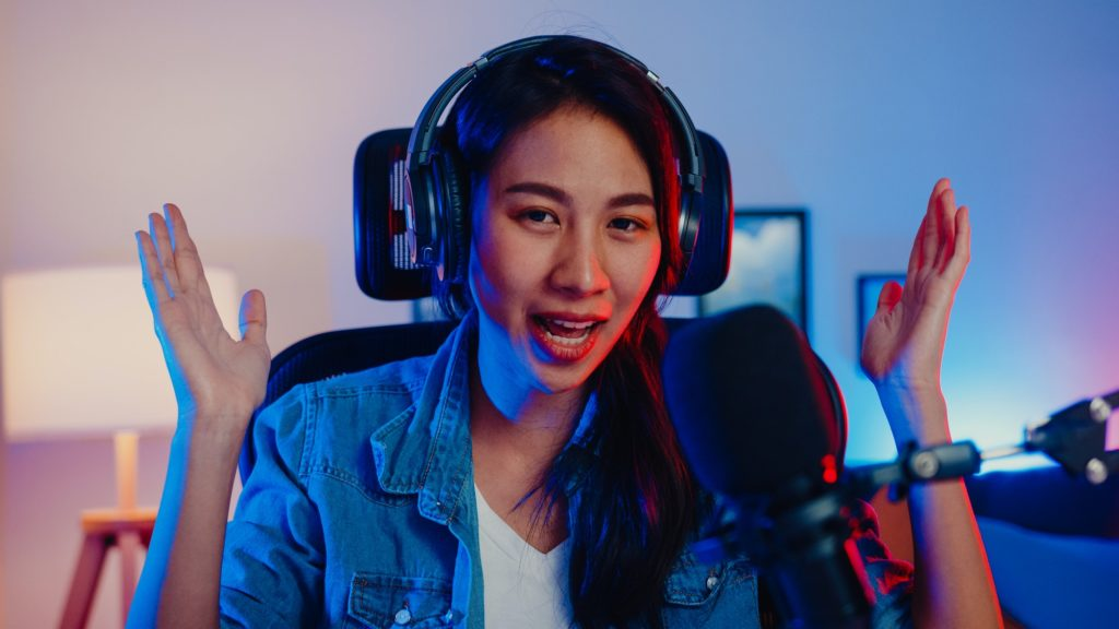 Happy asia girl blogger music influencer looking at camera broadcast record with audience in studio.